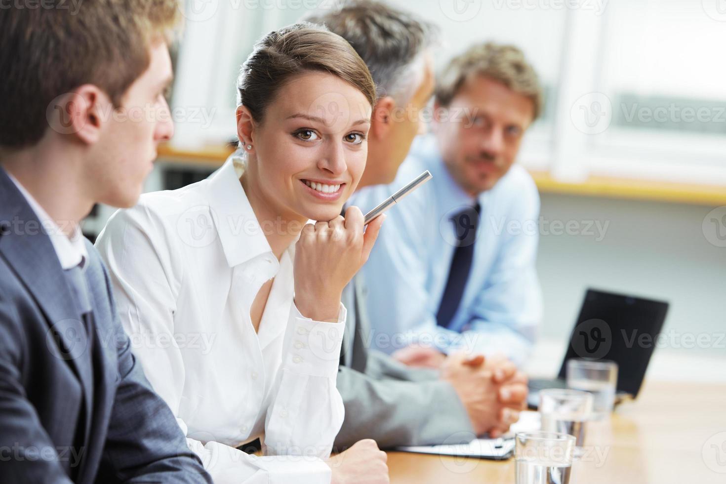 lachende vrouw die zit op een zakelijke bijeenkomst met collega's foto