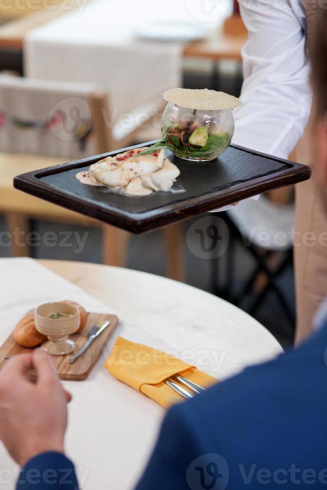 vrolijke jonge ober serveert een klant foto