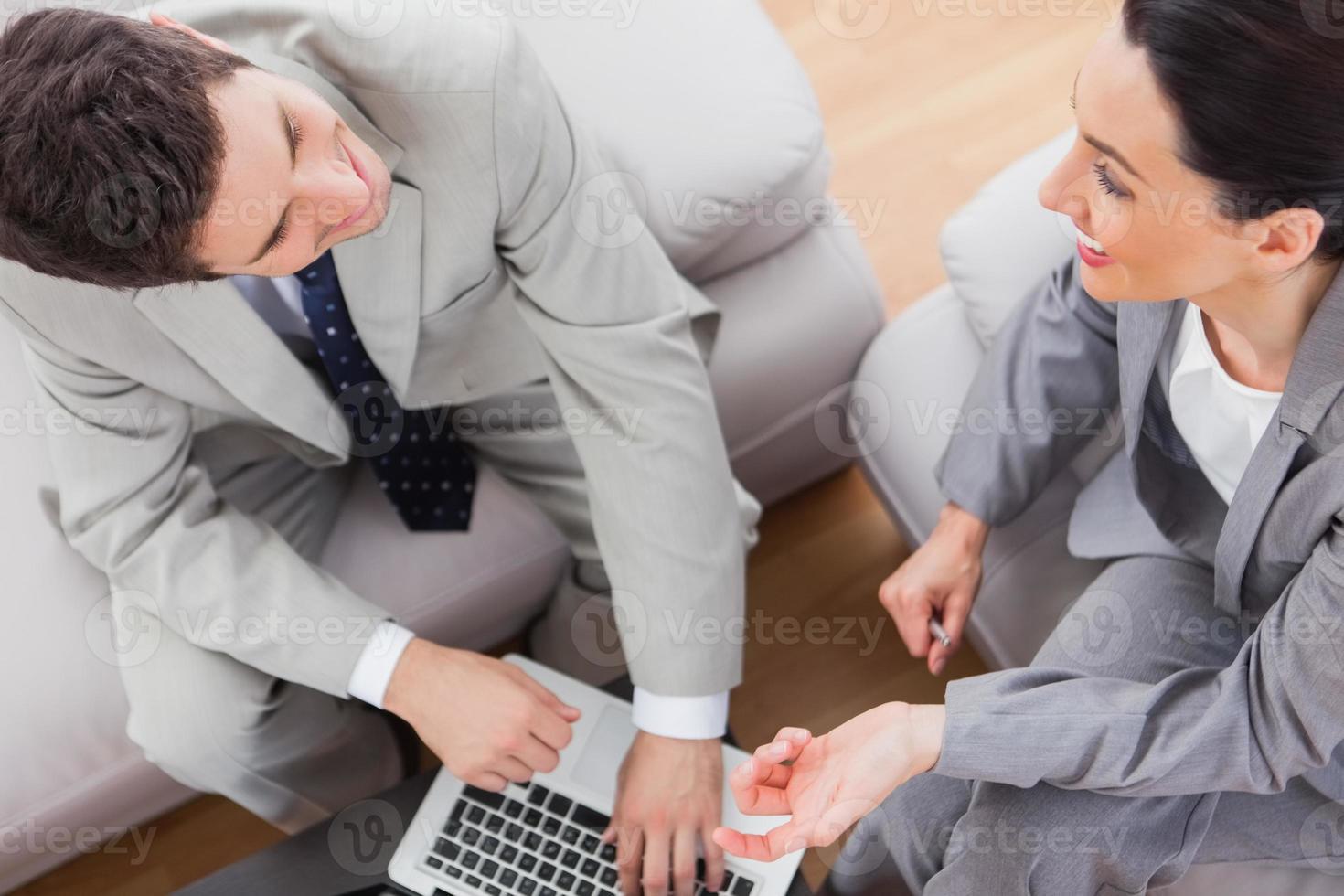 lachende collega's praten en met laptop zittend op de bank foto