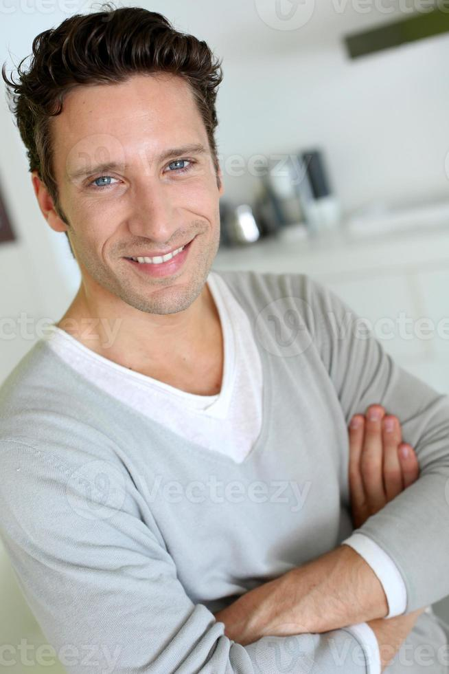 man met gekruiste armen in de keuken foto