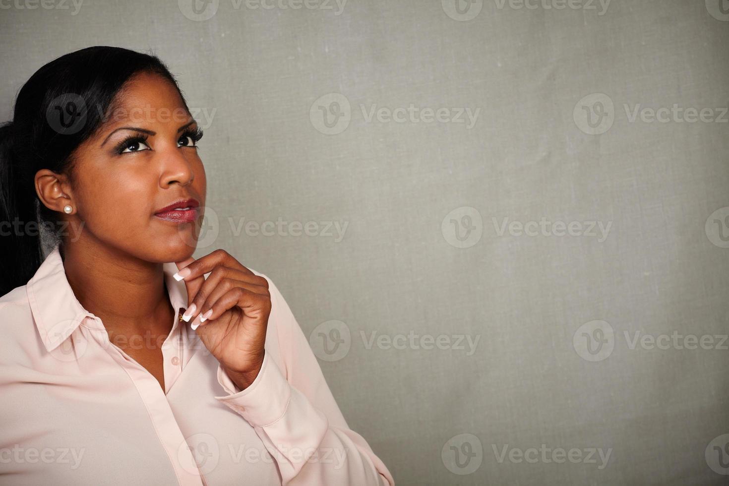 peinzende Afrikaanse vrouw die met hand op kin denkt foto