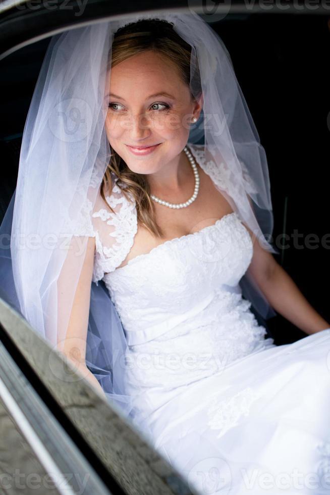 portret van een mooie jonge bruid die in de auto wacht foto