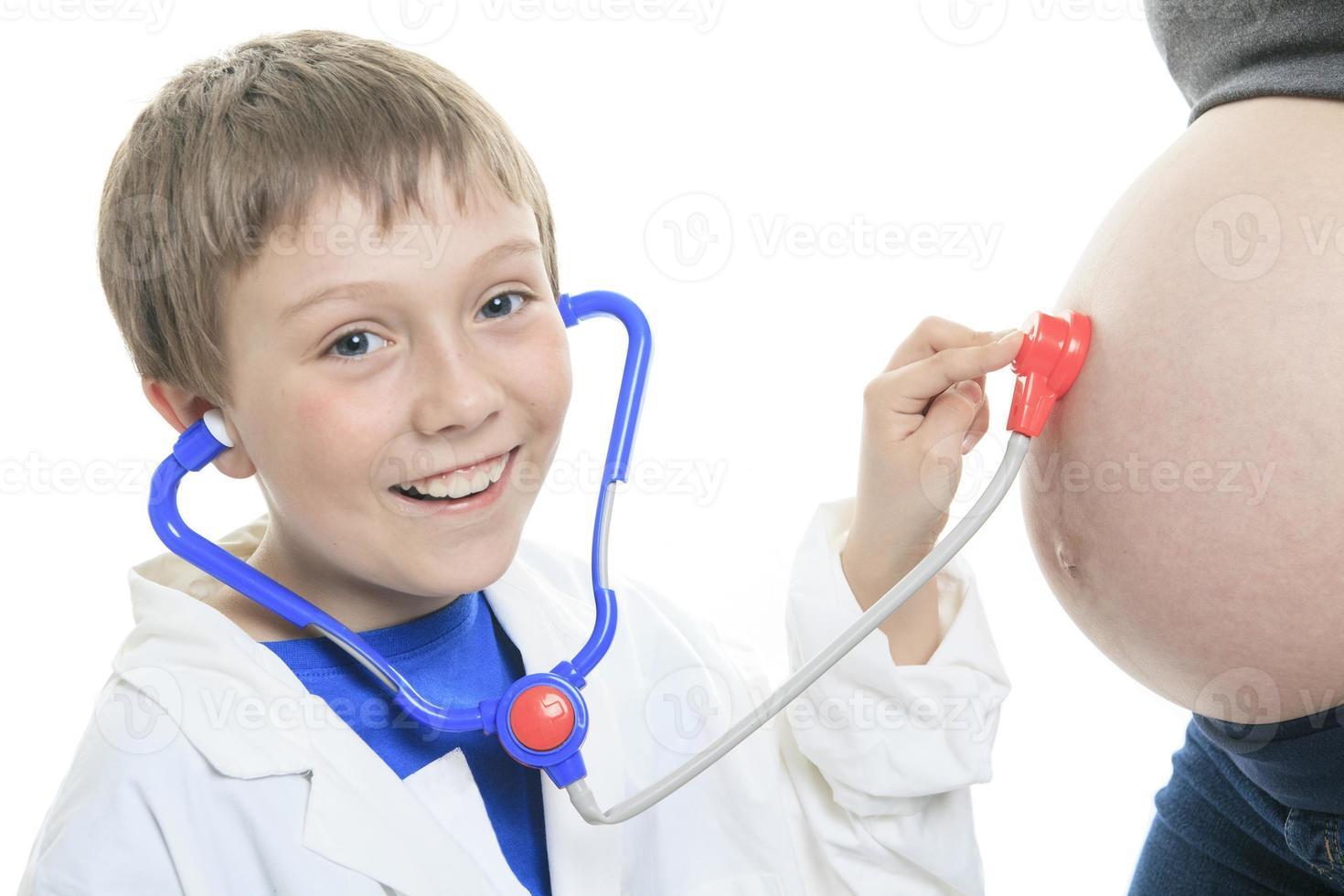 vrolijke kleine broer luisteren stethoscoop buik foto