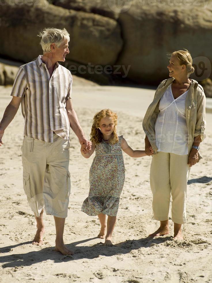 meisje lopen op het strand met haar grootouders. foto