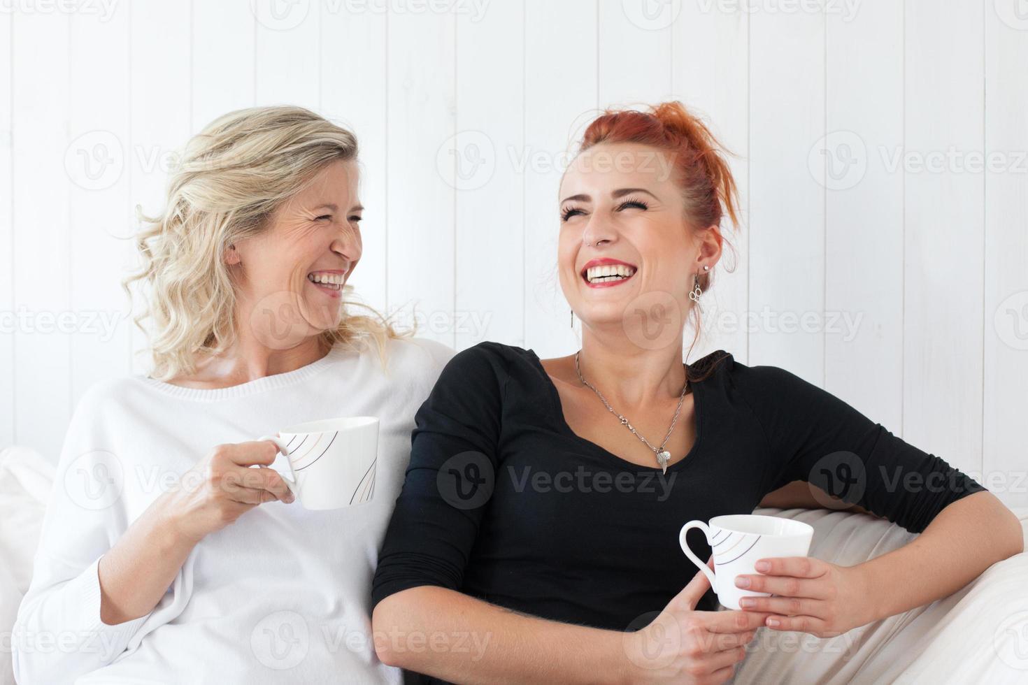 moeder en dochter zittend op de bank thuis foto
