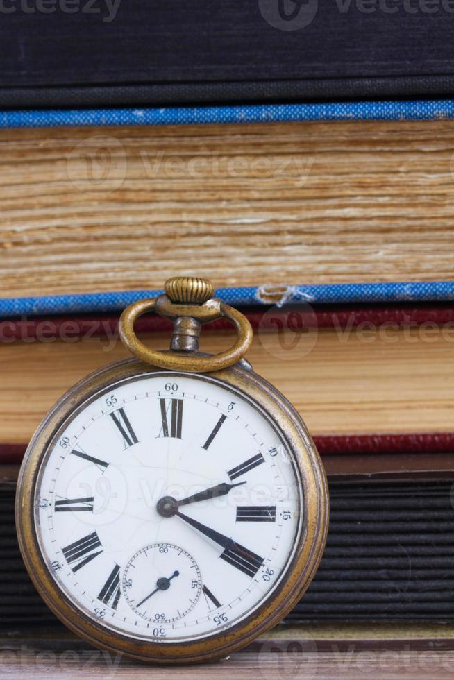 antieke klok op boeken achtergrond foto