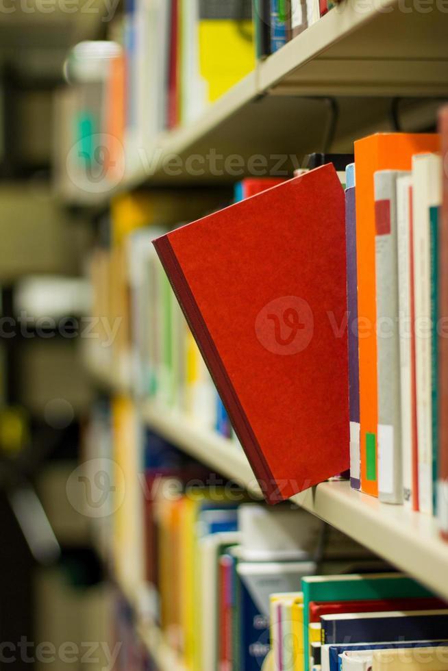 rood boek dat uit een boekenplank springt foto