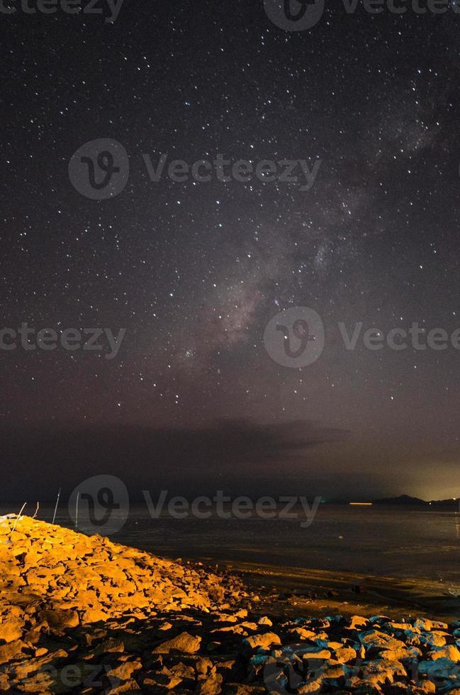 melkweggetjes over hemel met geel licht vervuiling op rotsformatie foto