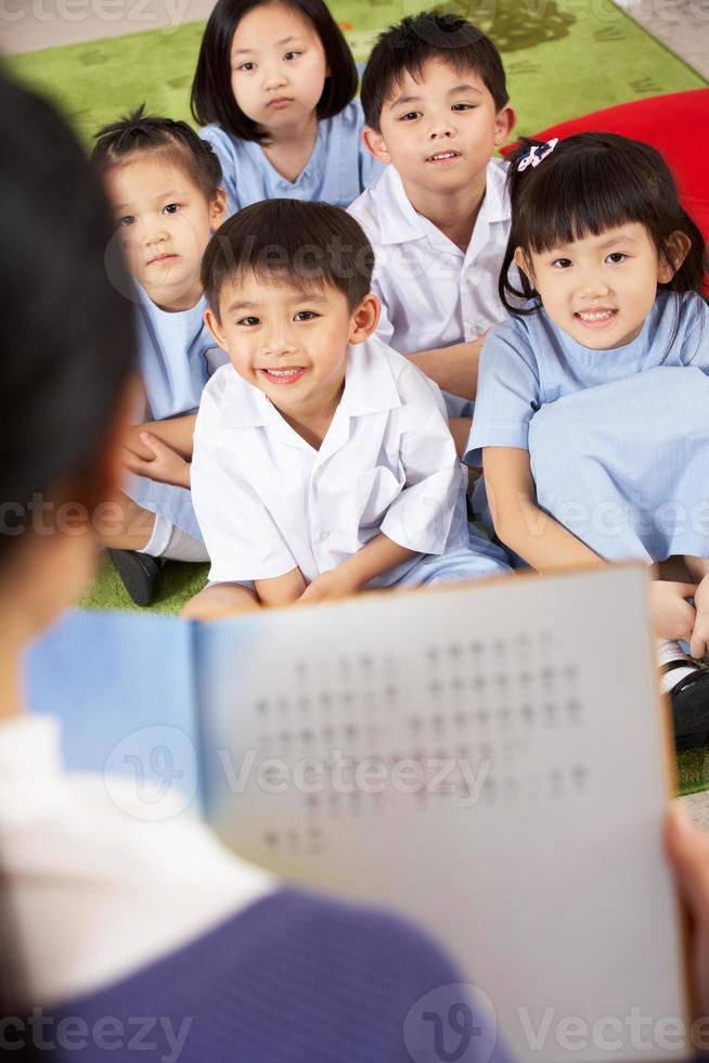leraar lezen aan studenten in de klas van de Chinese school foto