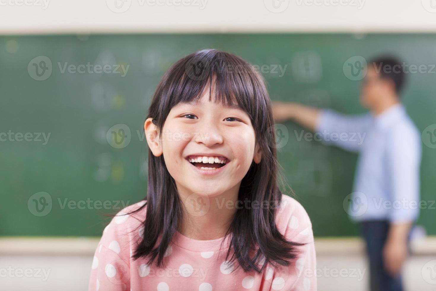 gelukkige leerlingen glimlachend in de klas met leraar foto