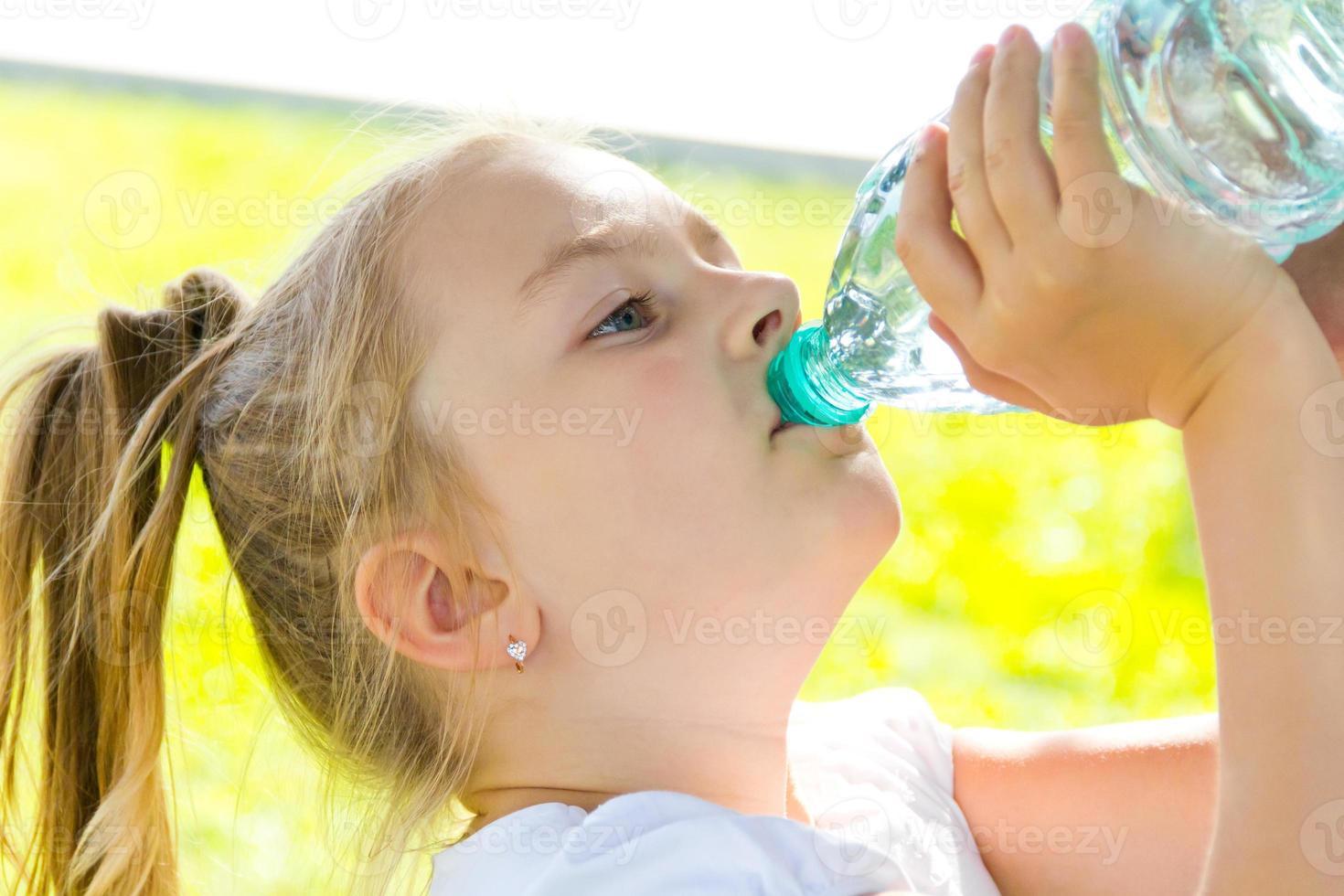 schattig meisje drinkwater foto