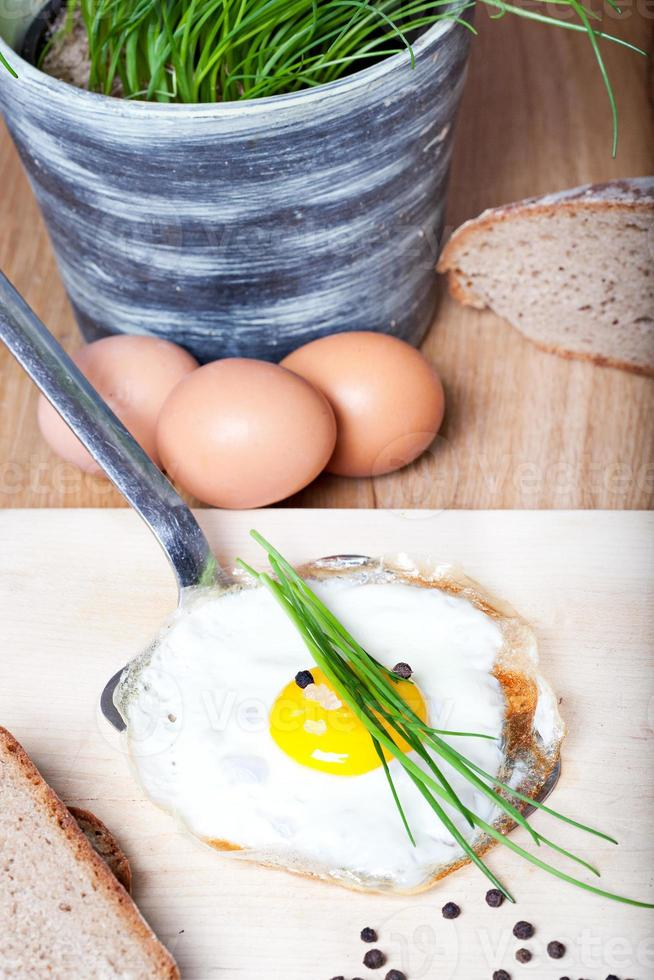 gebakken ei met kruiden op zilveren spatel foto