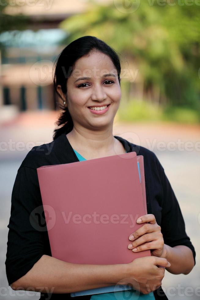 gelukkige jonge vrouwelijke student op universiteitscampus foto