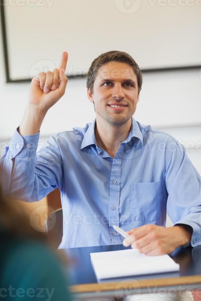 geamuseerde mannelijke volwassen student steekt zijn hand op foto
