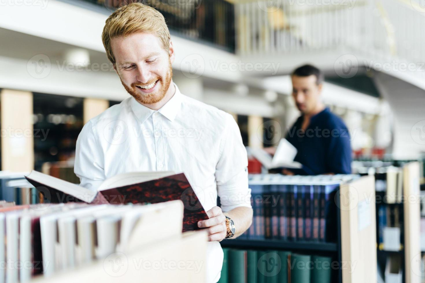 knappe student die een boek in een bibliotheek leest foto