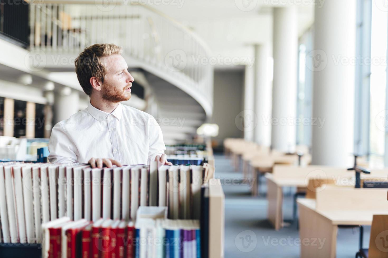 knappe student op zoek naar een boek in een bibliotheek foto