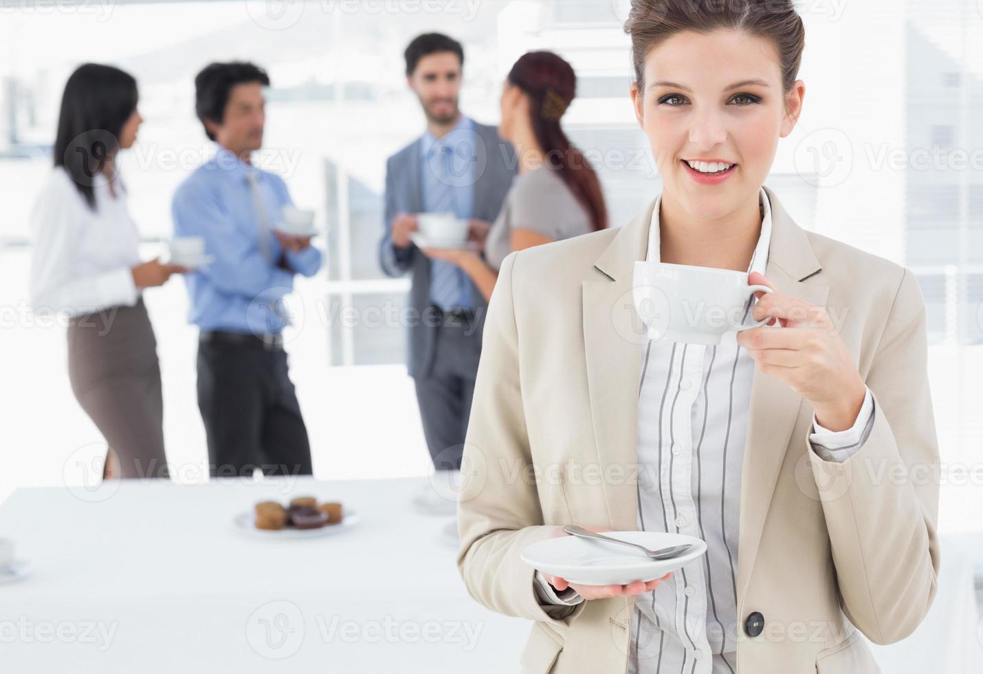 Glimlachende zakenvrouw met een drankje foto