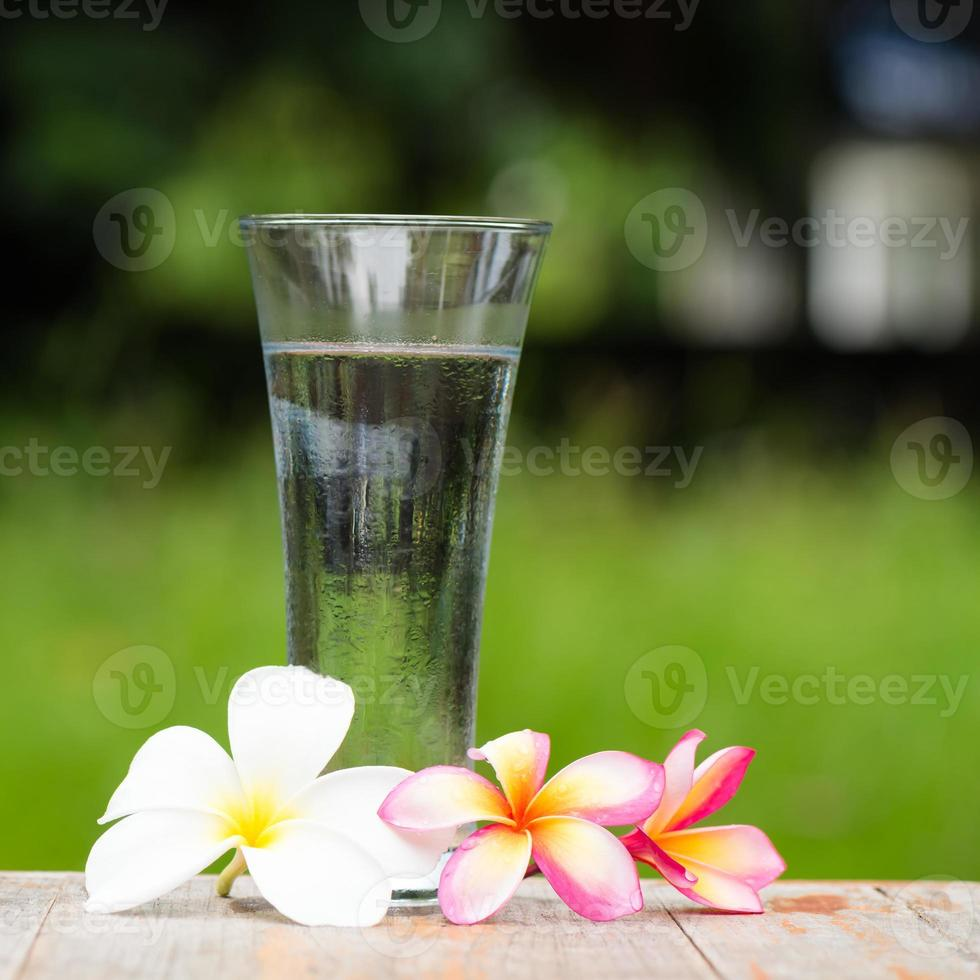 frangipani bloemen en drink water foto