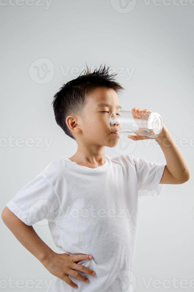 jongen drinkt water uit glas foto