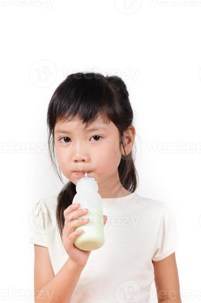 het jonge Aziatische meisje drinkt melk foto