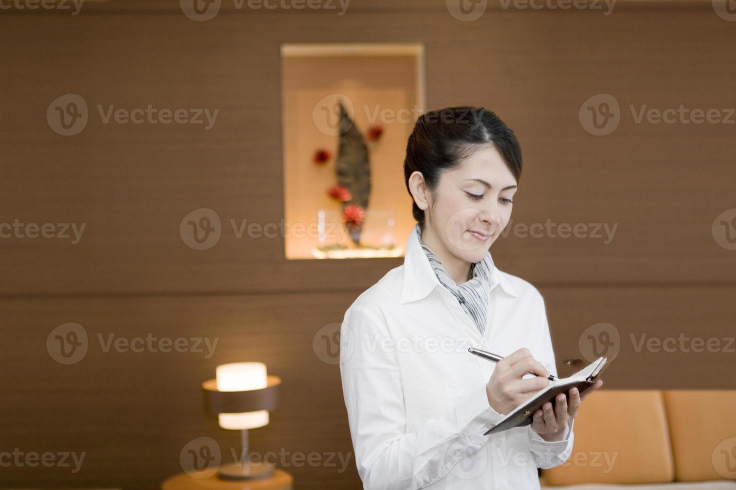 vrouw die een notitie op notitieboekje foto