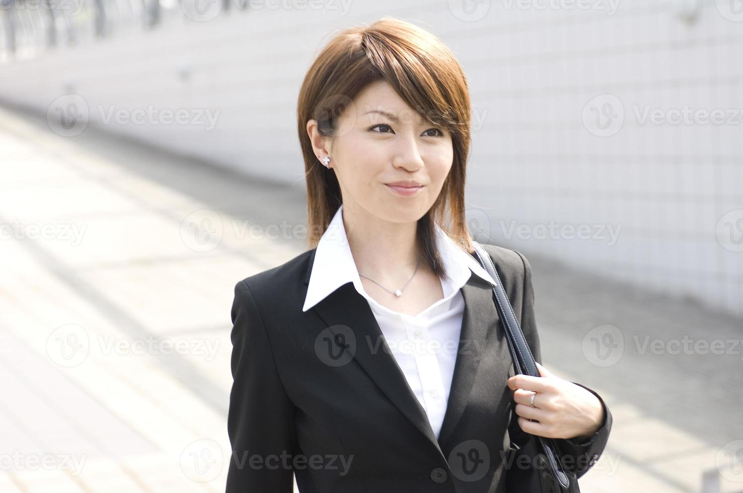 Japanse jonge vrouw die langs de stad loopt foto