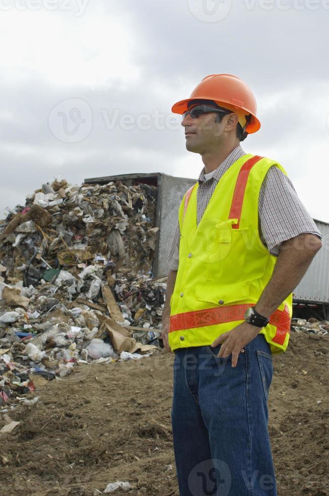 arbeider die zich dichtbij vrachtwagen stortend afval bevindt bij stortplaats foto
