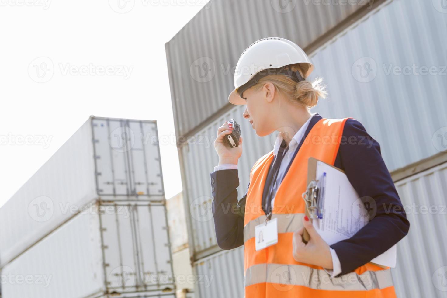 vrouwelijke ingenieur die walkie-talkie in scheepswerf gebruikt foto