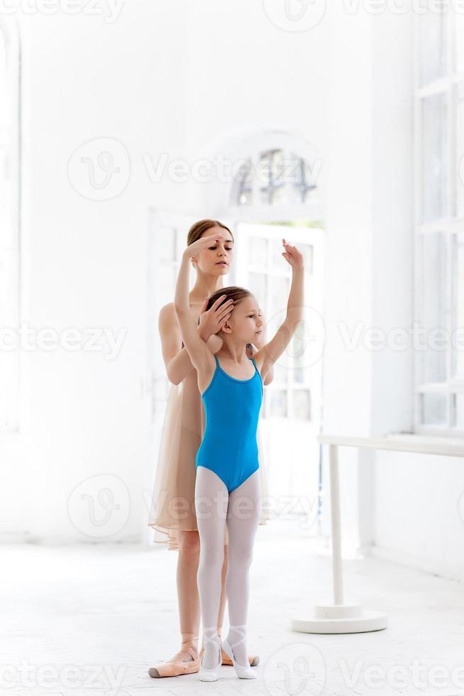 de kleine ballerina poseren bij ballet barre met persoonlijke leraar foto