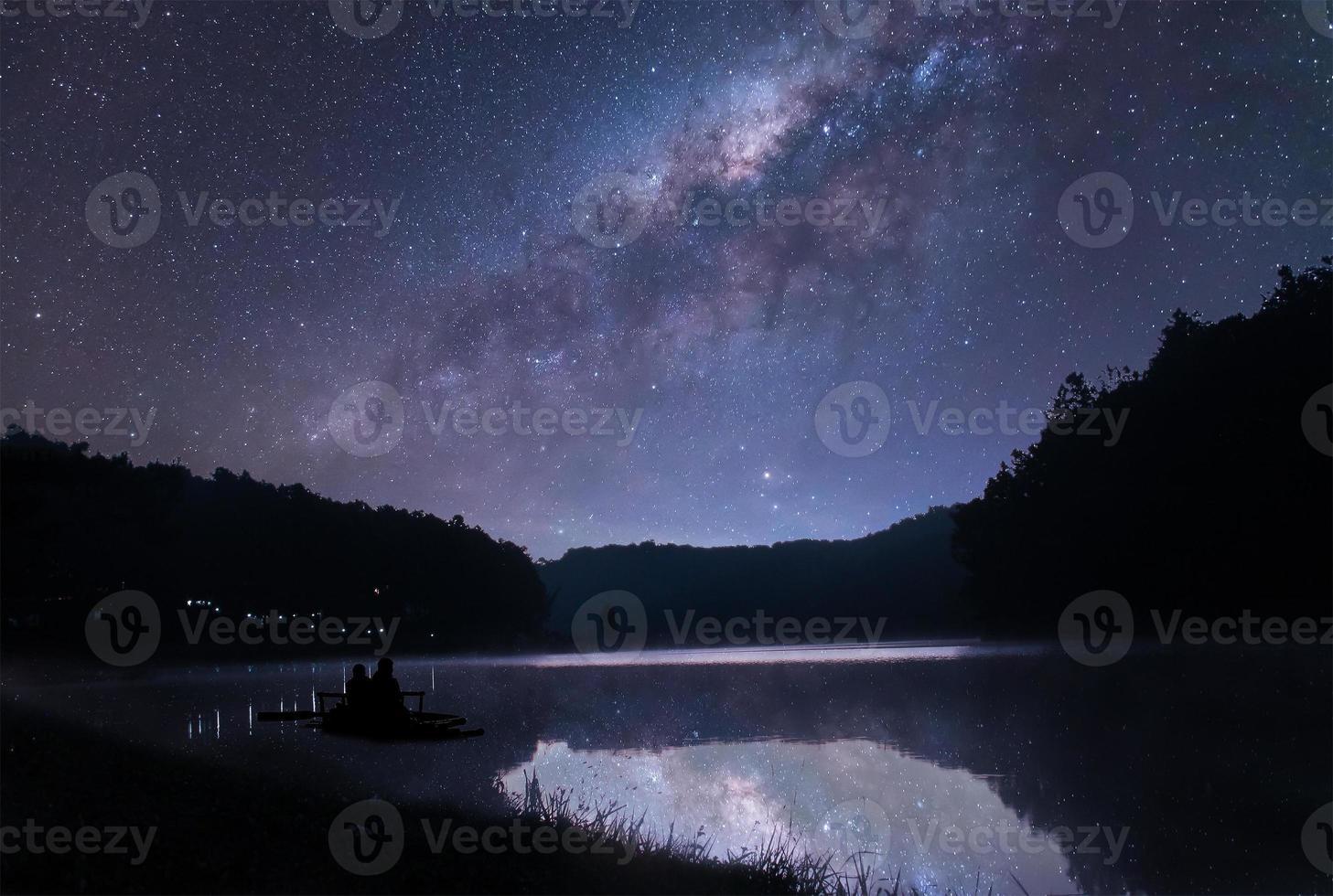 de melkweg boven het meer en een klein boad foto