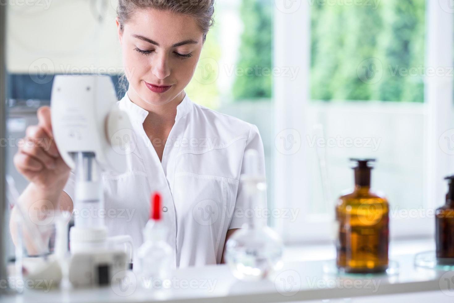 laboratoriumtechnicus die chemie-experiment doet foto