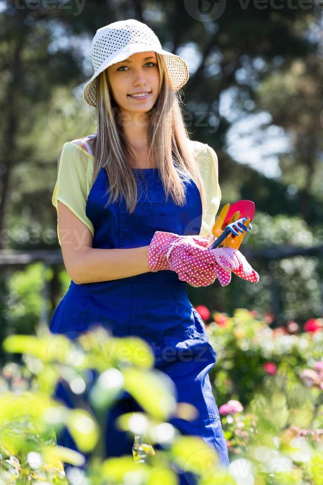 lachende jong meisje in uniform op tuinieren tuin foto