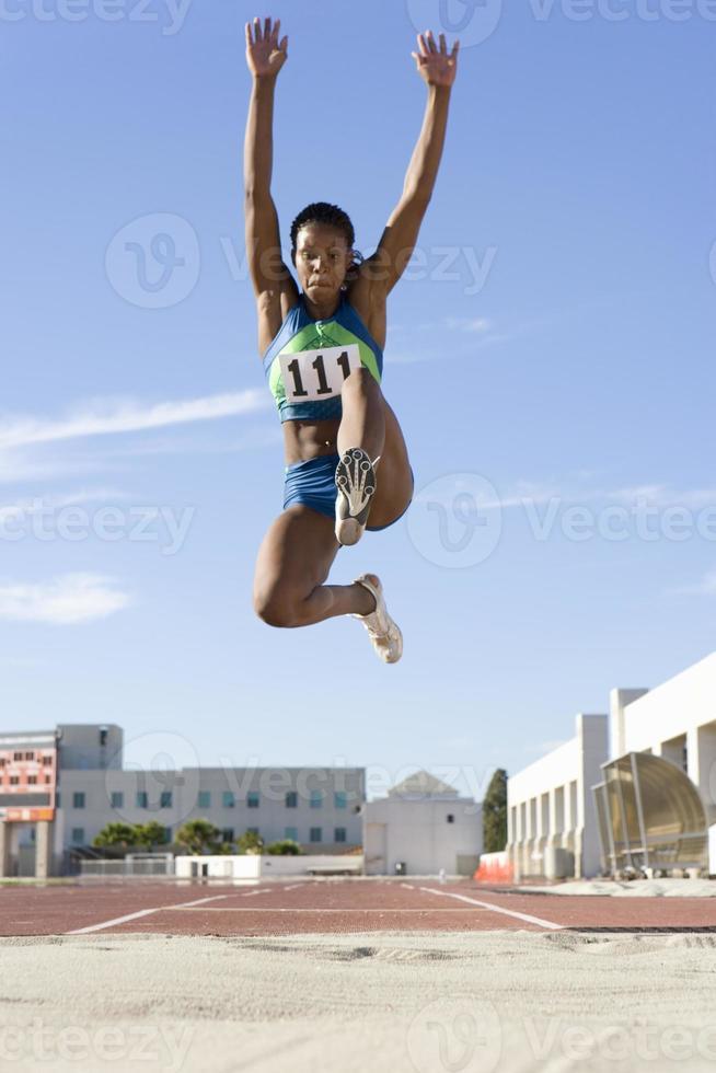Afrikaanse vrouwelijke atleet mid-air tijdens verspringen foto