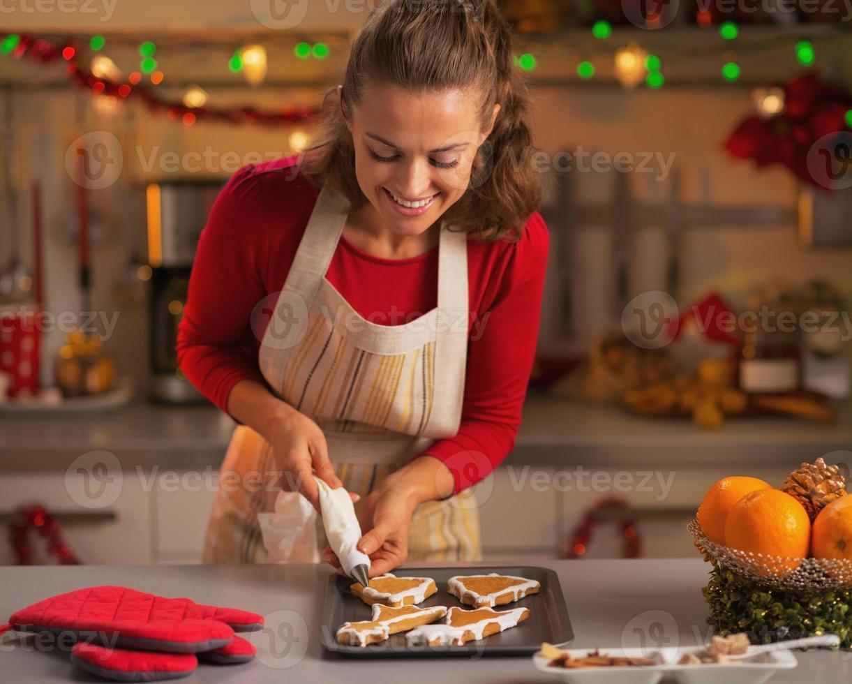 gelukkige jonge huisvrouw versieren kerstkoekjes in de keuken foto
