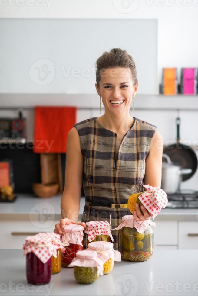 gelukkige jonge huisvrouw met potten van ingemaakte groenten foto