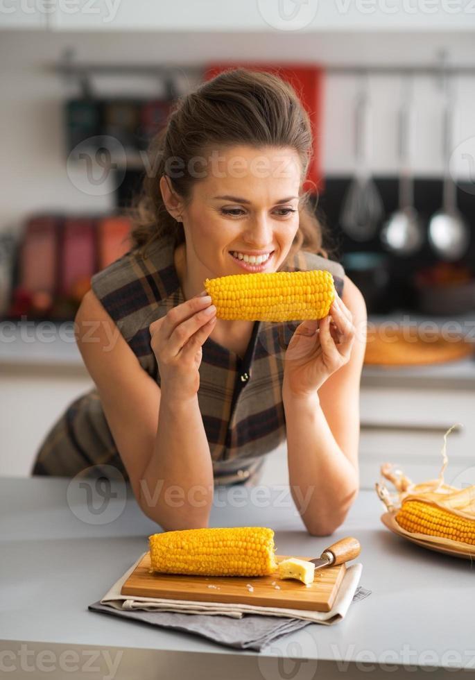 portret van gelukkige jonge huisvrouw die gekookt graan in keuken eet foto