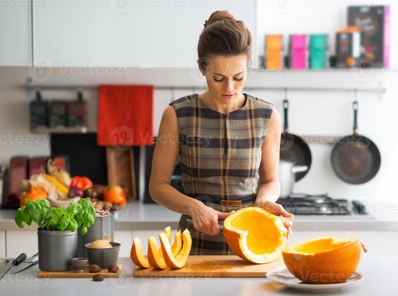 jonge huisvrouwen snijdende pompoen in keuken foto