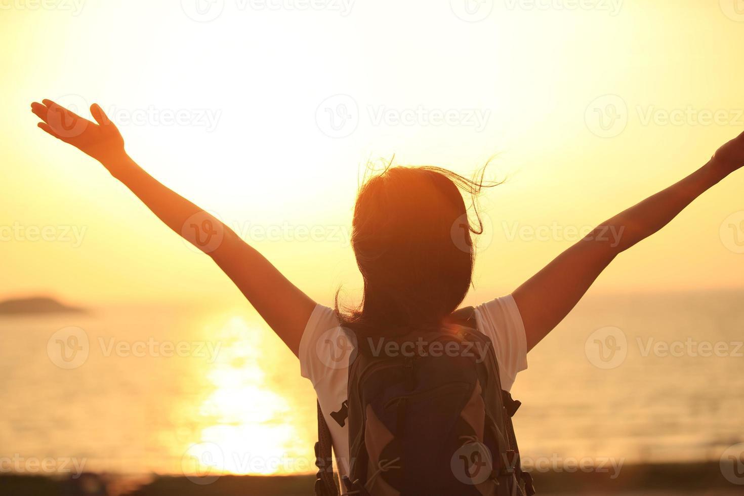 juichende wandelende vrouw zonsopgang aan zee foto