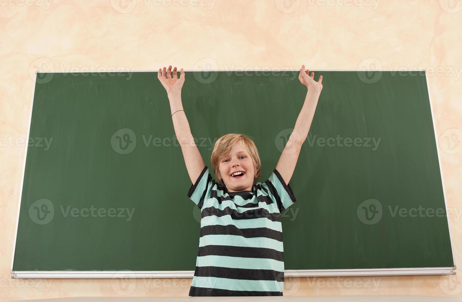 jongen juichen voor schoolbord foto