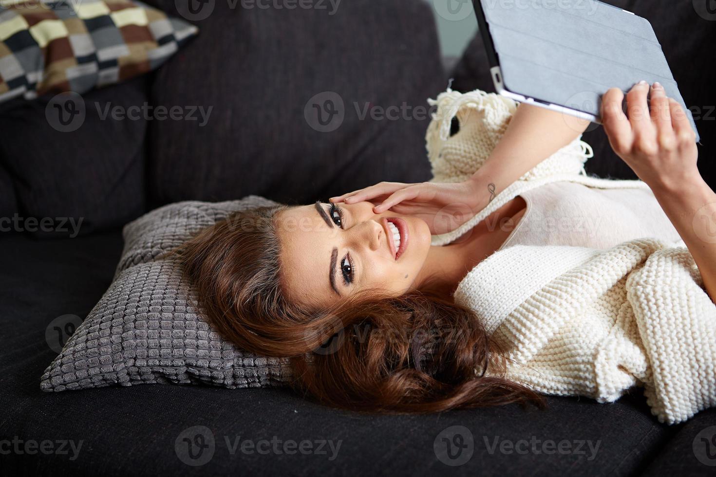 vrolijke vrouw liggend op een gezellige bank foto