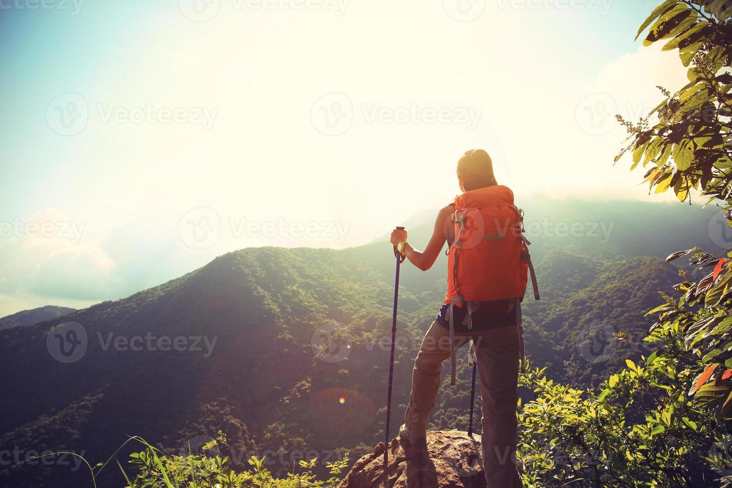 juichende vrouwenwandelaar die aan bergpiek beklimt foto