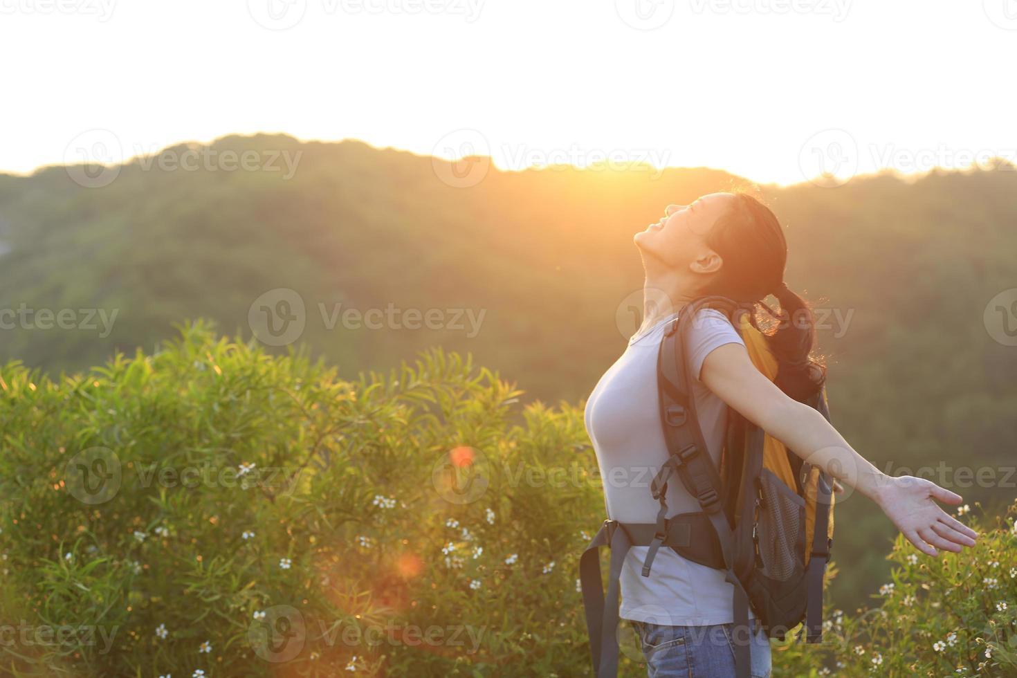 juichende vrouw wandelaar open armen met zonsopgang foto