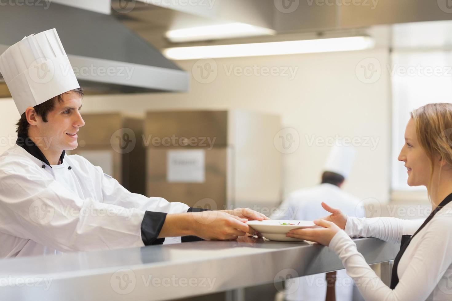 chef-kok een bord geven aan de serveerster foto