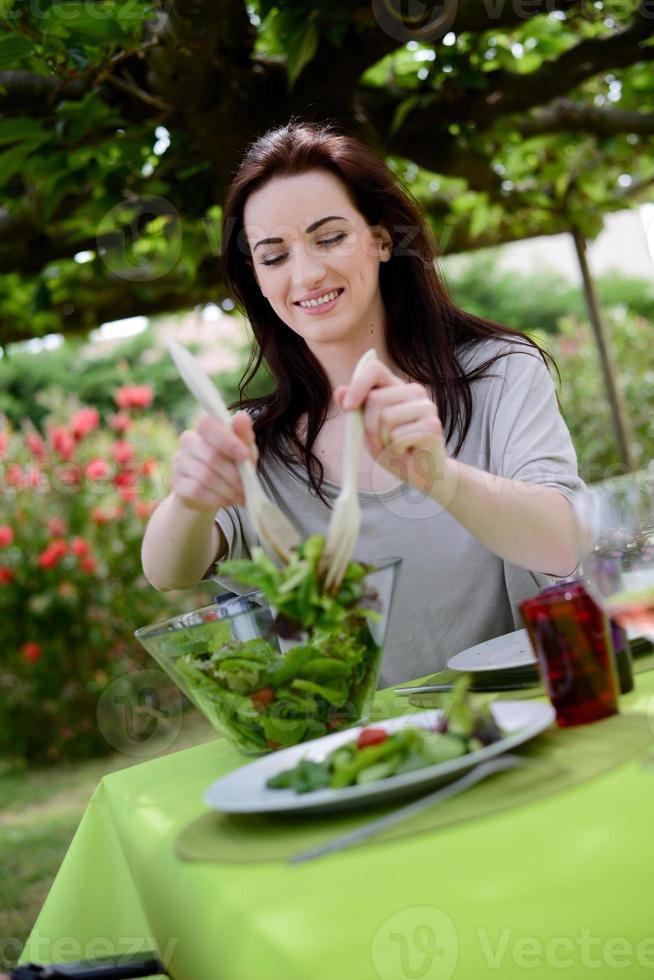 vrolijke jonge vrouw salade serveren op barbecue feest buiten foto