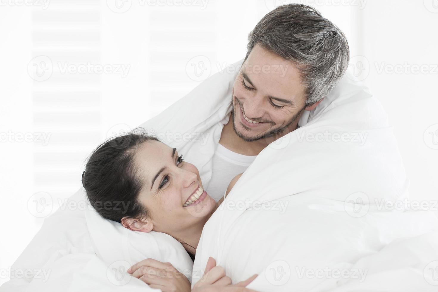 vrolijk jong stel gewikkeld in hun quilt foto