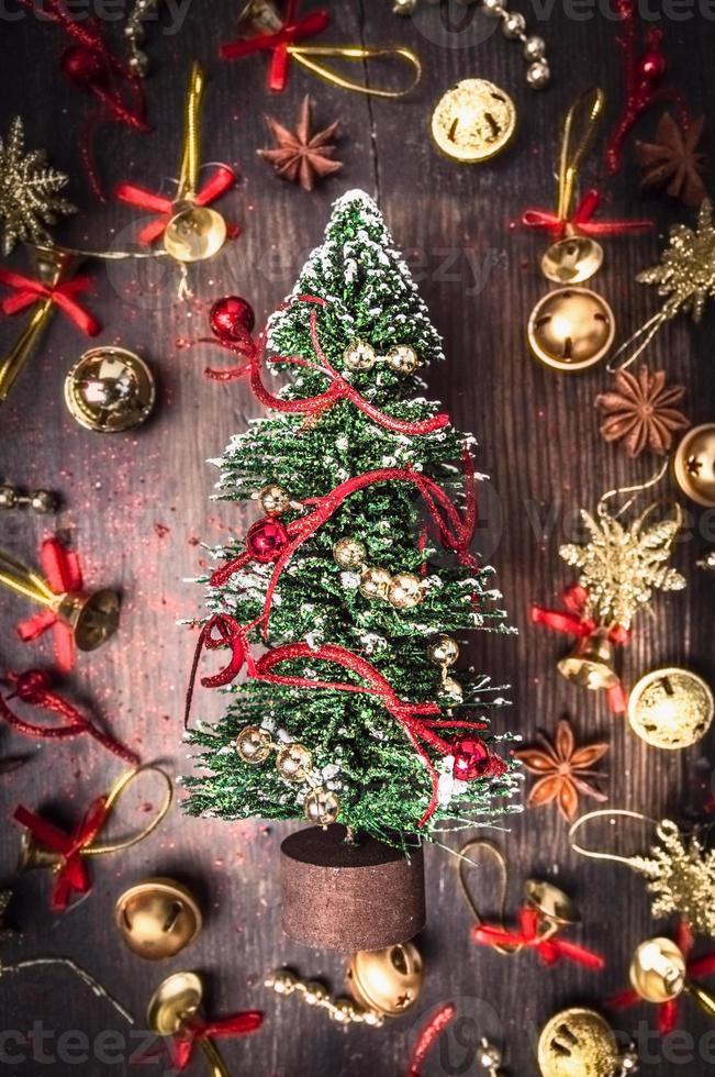 Kerstkaart met dennenboom, gouden en rode decoraties foto