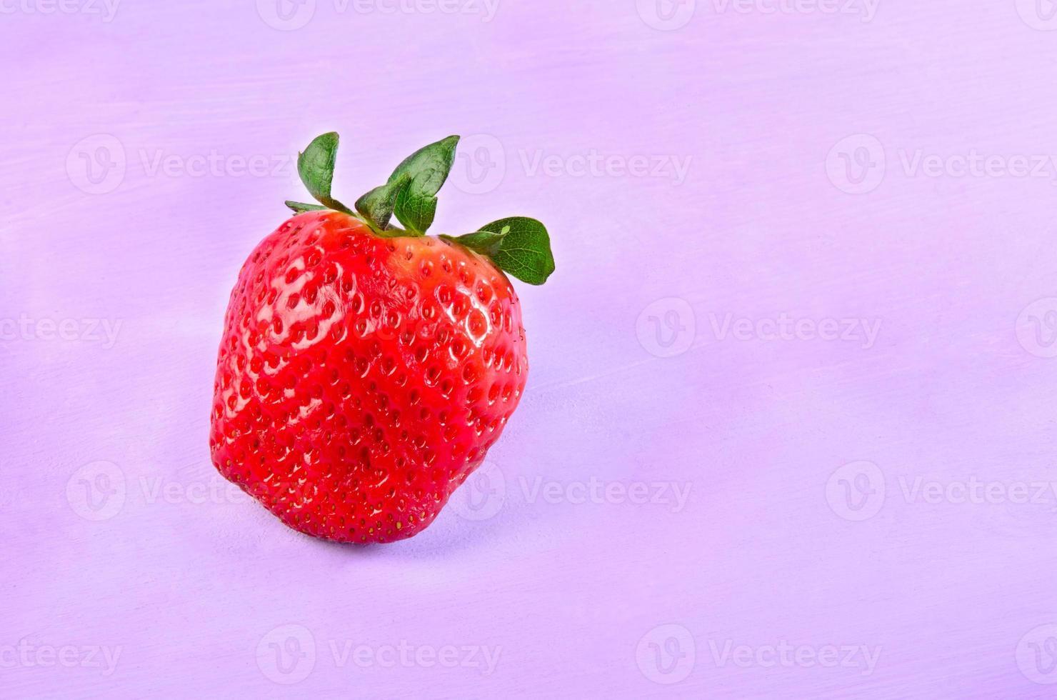 rijpe aardbeien op een paarse achtergrond met kopie ruimte foto