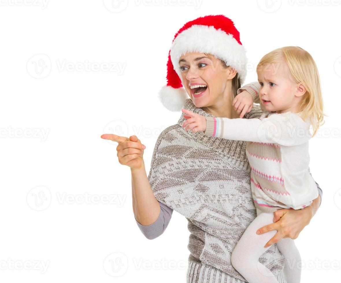 glimlachende moeder en babymeisje die op exemplaarruimte richten foto