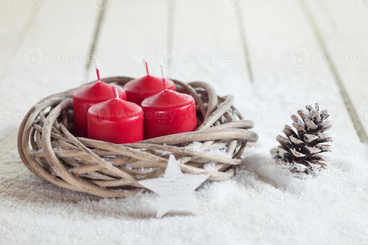krans, rode kaarsen, houten ster, dennenappel, kopie ruimte foto
