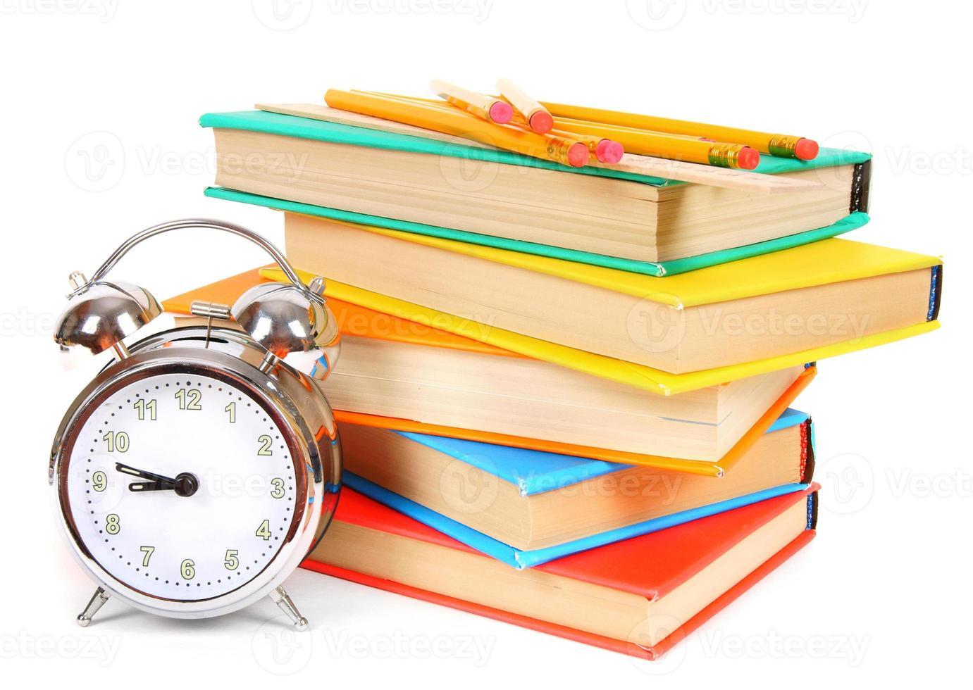 wekker en veelkleurige boeken. foto
